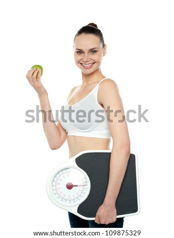 Attractive woman with apple and weight scale smiling at camera - stock photo