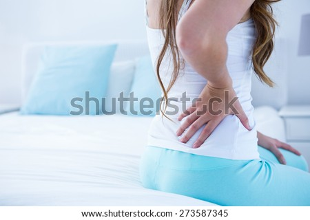 Attractive woman with back pain at home in the bedroom - stock photo