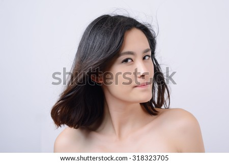 Attractive  woman  with bare shoulders looking at the camera with a friendly smile