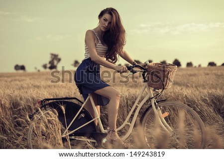 Attractive woman with bike in wheat field - stock photo