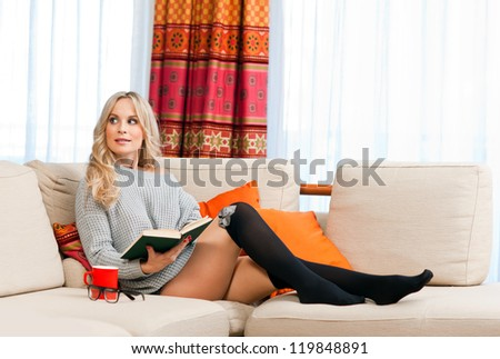 attractive woman with book in her home sofa