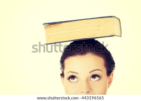 Attractive woman with book on head - stock photo