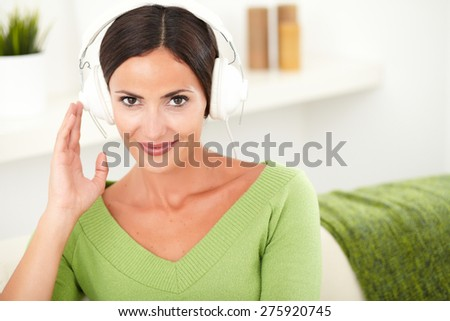 Attractive woman with brown hair calmly listening to music while looking at the camera - copy space - stock photo