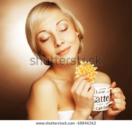 attractive woman with coffee and cookies - stock photo