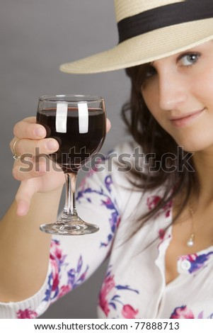 Attractive woman with colorful shirt and white hat toasting with wine - stock photo
