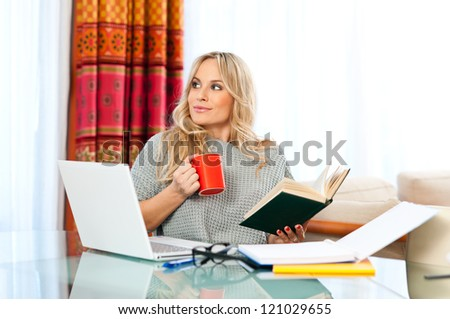 attractive woman with cup of coffee, book and laptop sitting at her home desk and working - stock photo