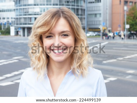 Attractive woman with curly blond hair outside in the city - stock photo