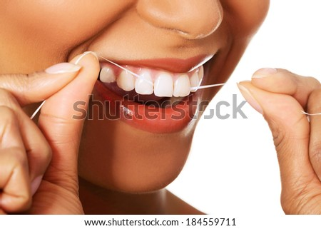 Attractive woman with dental floss. Closeup.  Mouth and teeth. Isolated on white. - stock photo