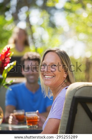 Attractive woman with friend on vacation at table - stock photo