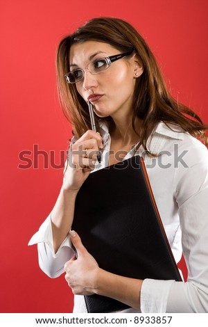 Attractive woman with glasses and Folder, holding a pen to her mouth while posing thoughtfully. - stock photo