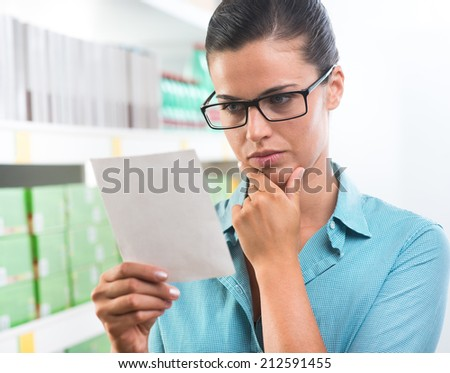 Attractive woman with glasses holding a shopping list at supermarket. - stock photo