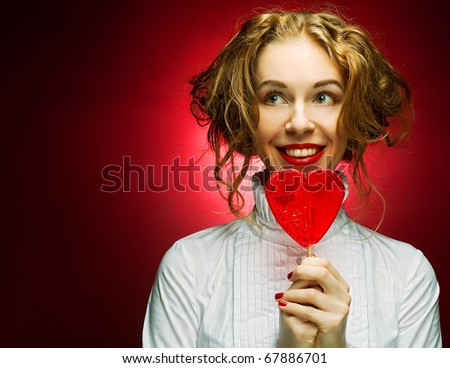 attractive woman with heart caramel over red background - stock photo