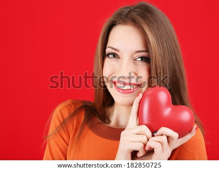 Attractive woman with heart, on red background - stock photo