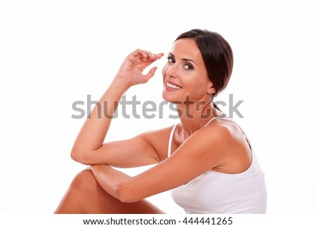 Attractive woman with her knee up and her hand to face while looking at camera and wearing a white tank top, hair tied back isolated - stock photo