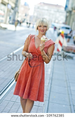 attractive woman with ice cream on the street - stock photo
