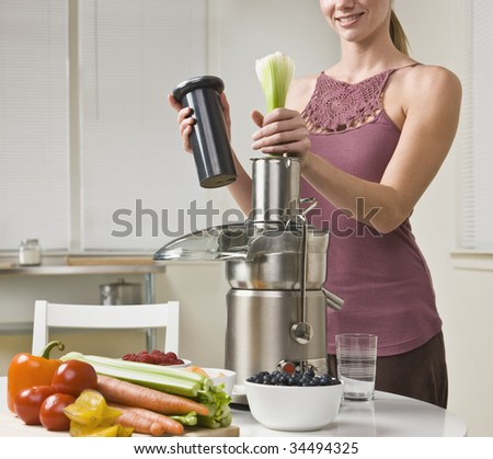 Attractive woman with juicer machine, adding celery and smiling. Horizontal. - stock photo