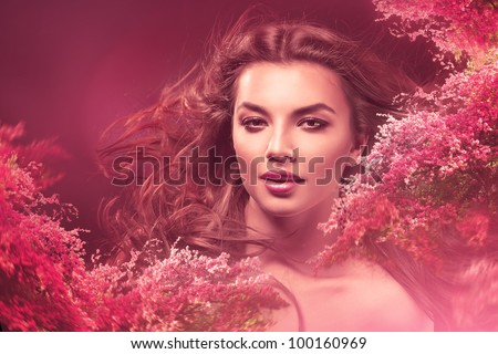 attractive woman with long hair in flowers - stock photo