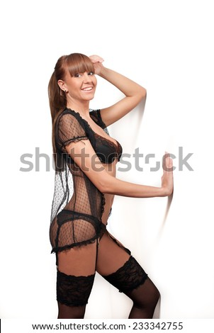 Attractive woman with long legs in black stockings posing near a wall. Side view of perfect body woman in lingerie. Classic boudoir shot. Erotic photo.