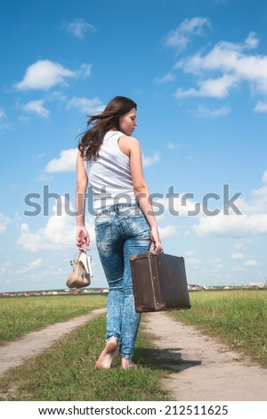 Attractive woman with old suitcase goes afar on unpaved road