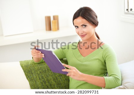Attractive woman with pulled back hair looking at the camera while holding a tablet - stock photo