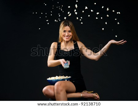 attractive woman with remote control and popcorn - stock photo
