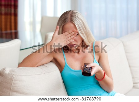 attractive woman with remote control cover her eyes - stock photo