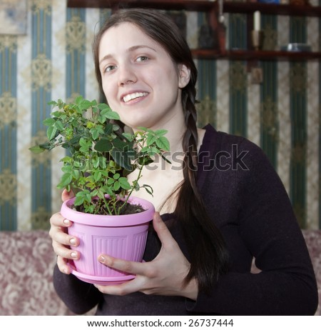 Attractive woman with rose flower in the pot at her home