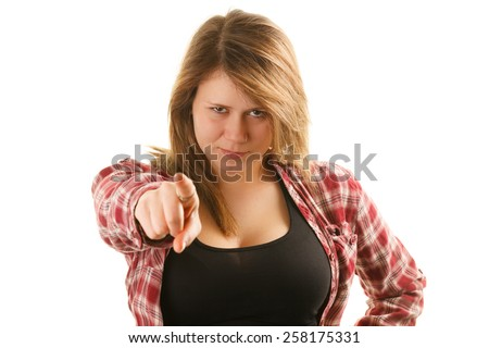 Attractive woman with serious smirk and pointing into camera - stock photo