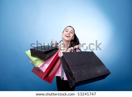 Attractive woman with shopping bags on blue background - stock photo