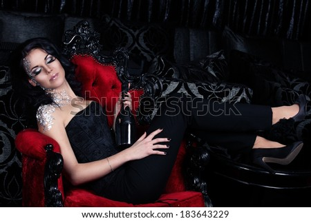 Attractive woman with silver makeup is having a party and holding silver champange bottle in her hands sitting on the red vintage gothic chair