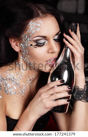 Attractive woman with silver makeup is having a party and touching the bottle of champagne with her pink lips - stock photo