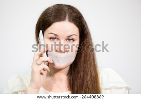 Attractive woman with tape on mouth trying to call mobile phone, grey background - stock photo