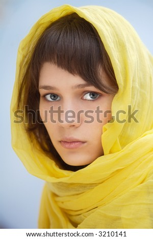 attractive woman with veil in the head a over blue background (focus in the eye) - stock photo