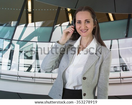Attractive woman working in a call center. Portrait in office against of glass reflection