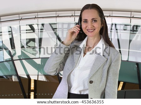 Attractive woman working in a call center. Portrait in office against of glass reflection - stock photo