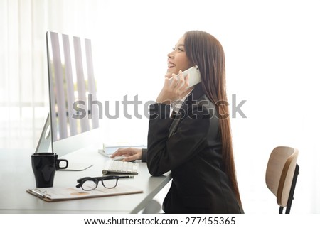 Attractive woman working in office on laptop - stock photo
