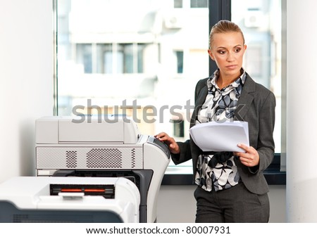 attractive woman working on copy machine in office - stock photo