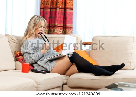 attractive woman working on her laptop in her living room sofa - stock photo