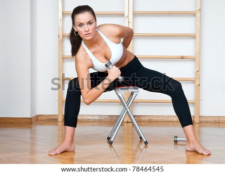 attractive woman working out with weights in gym - stock photo