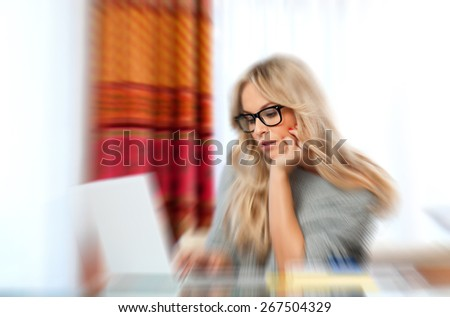 attractive woman writer in her home with laptop in creative process, zoomed for dramatic effect