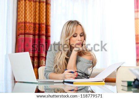 attractive woman writer in her home with laptop thinking expression - stock photo