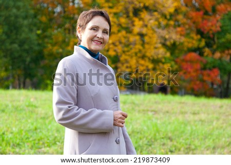 attractive woman 50 years in the autumn park - stock photo