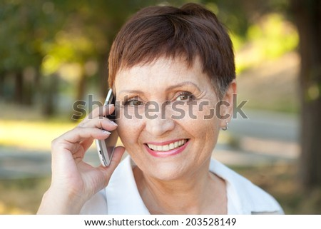attractive woman 50 years in the park with a mobile phone - stock photo