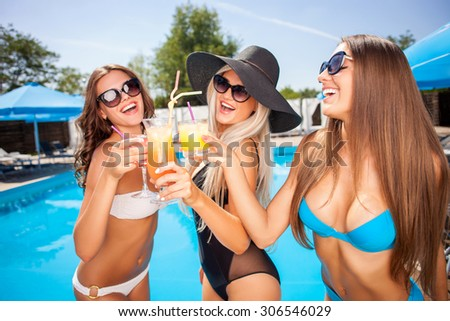 Attractive women are drinking cocktails near a swimming pool. They are standing and smiling. The friends are wearing swimwear and sunglasses - stock photo