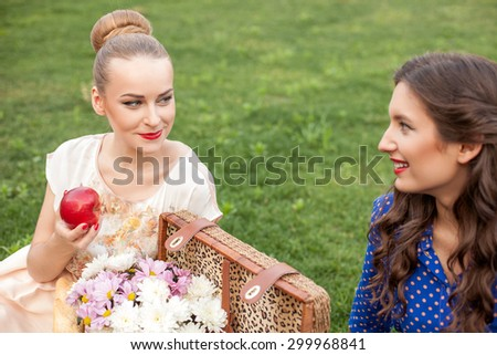Attractive women are sitting on grass and relaxing. The blond girl is eating an apple with appetite. The friends are looking at each other with happiness and smiling - stock photo