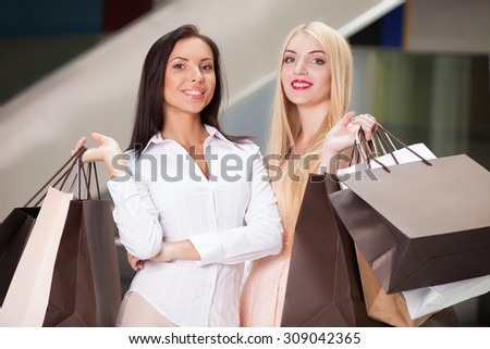 Attractive women are standing and posing in shopping center. They are holding many packets of bought things in their hands. They are showing it boastfully and smiling - stock photo