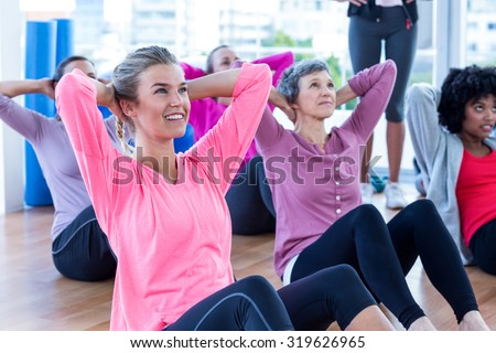 Attractive women doing sit ups on hardwood floor at fitness studio - stock photo