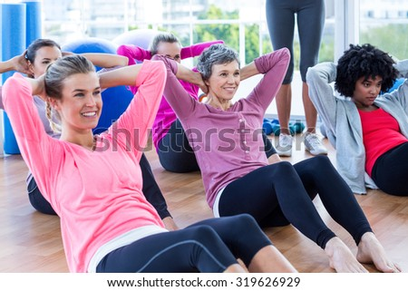 Attractive women doing sit ups on hardwood floor in fitness studio - stock photo