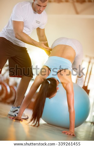Attractive women exercise on the ball in the gym with the help of personal instructors - stock photo