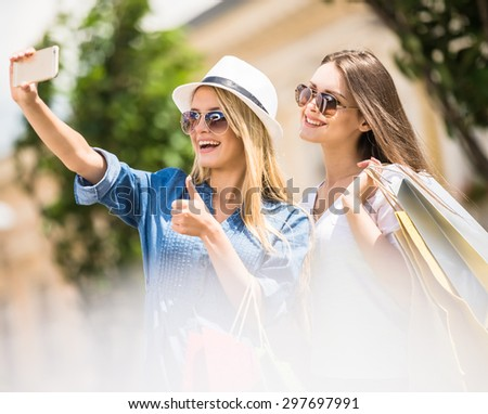 Attractive women in sunglasses taking a selfie with their cell phone. Side view. - stock photo